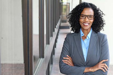 smiling business professional woman standing outside wearing gray suit with arms crossed depicting professional resume services