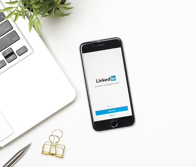 white desk with laptop plant pen and iphone showing LinkedIn depicting LinkedIn makeover and profile writing services