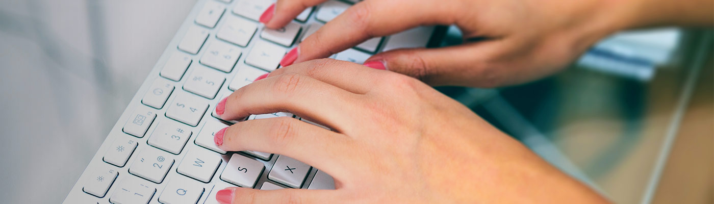 closeup of woman's hands with bright pink nail polish typing on keyboard depicting browsing executive resume samples